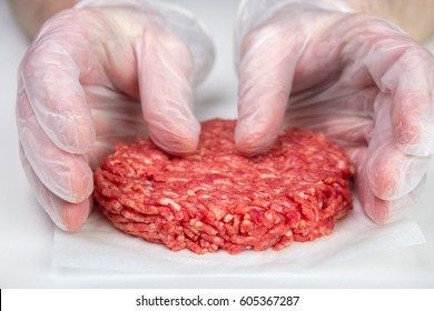 Hand shaping burger patty with disposable vinyl gloves