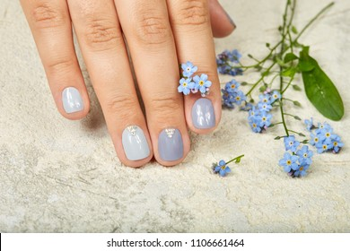 Hand with short manicured nails colored with gray nail polish, decorated with gemstones and forget me not flowers