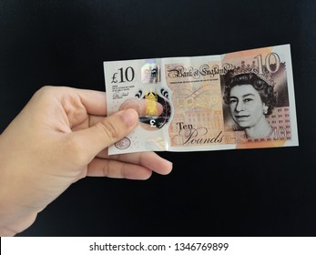 Hand showing 10 Pounds BANK OF ENGLAND banknote with black background/selective focus.