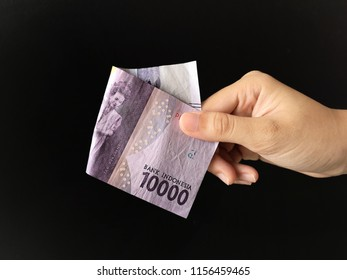 Hand showing 10000 rupiah Indonesian money with black background.