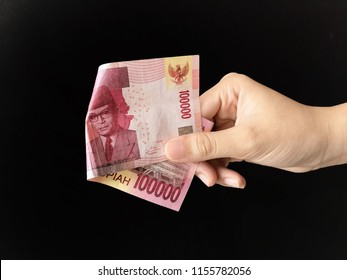 Hand showing 100000 rupiah Indonesia money with black background