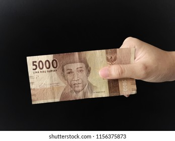 Hand showing 5000 rupiah Indonesian money with black background.
