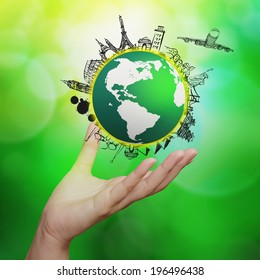 hand showing airplane traveling around the world on green nature background as concept