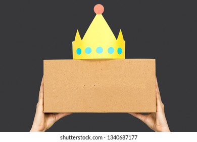 Hand showing a box with yellow paper crown and blank space in front for text. Concept of leadership or trending topics.