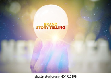 hand showing BRAND STORY TELLING  text on light bulb , business concept