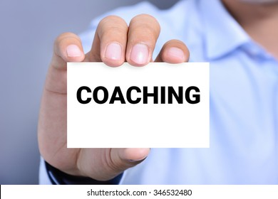 Hand showing card with COACHING word