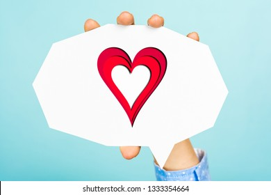Hand showing a heart shape on empty white speech bubble with straight cutting shape, all this on blue background.