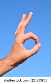 Hand showing Ok symbol. All is fine, against the blue sky