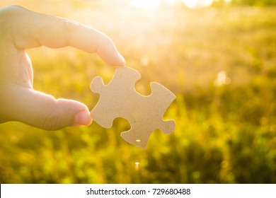 Hand showing one piece of puzzle, jigsaw against green grass field meadow background. sunny day. sun rays.