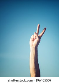 Hand showing peacy victory sign against pure blue sky