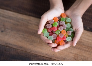 hand showing pile of gumdrop on a wooden table background