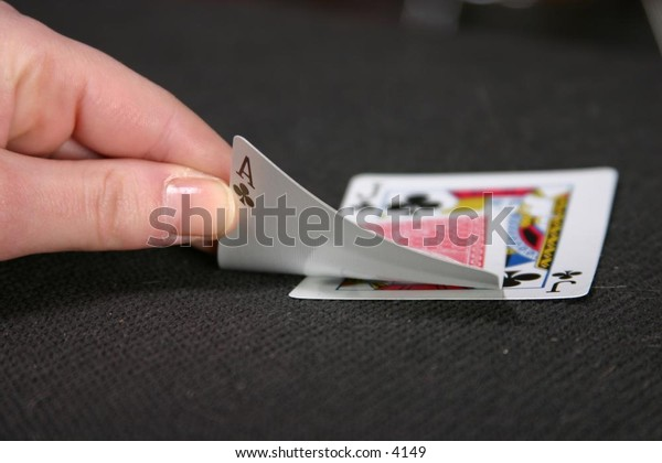hand showing playing cards on table