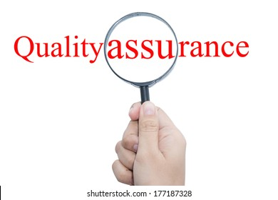 Hand Showing quality assurance Word Through Magnifying Glass