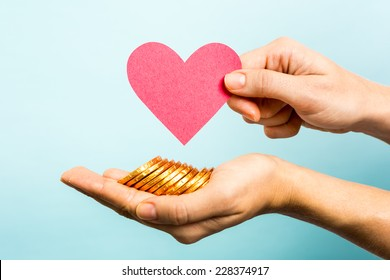Hand showing red heart paper shape and coins on blue background. Love and money concept.