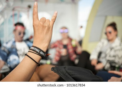 A hand showing the sign of the horns, whichs usually refers to the appreciation of rock music. The wristband says Festival 2018. A group of friends is sitting, chatting and drinking in the background.