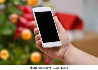 Hand showing a smart phone with a Christmas tree background at home