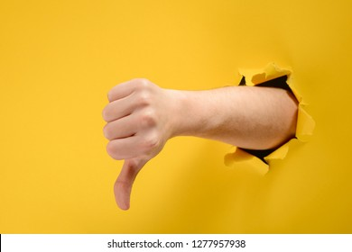Hand showing a thumb down through ripped hole in yellow paper background. Dislike and disapproval gesture.