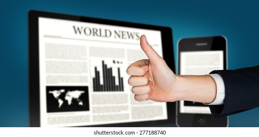 Hand showing thumbs up against digital tablet and smartphone showing news