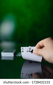 Hand showing two poker cards on the table with reflection on green background with copy space