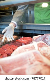 A hand showing the various meat options at a fresh meat counter