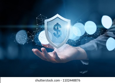Hand shows a shield with dollar sign on dark background. Concept of protection money.