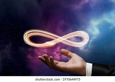 Hand shows the sign of infinity on the background of outer space.