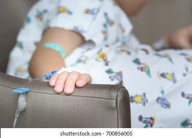 Hand of sick boy on the sofa in hospital, little boy sick in the Hospital with saline intravenous (iv)