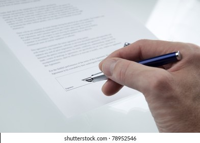 A hand signing a business contract