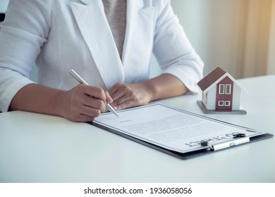 Hand signing on contract after the real estate agent explains the business contract, rent, purchase, mortgage, a loan, or home insurance to the buyer.