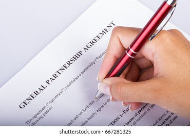 Hand signing a Partnership Agreement, closeup shot for any kind of legal agreements and joint venture deal topics