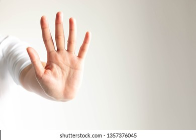 A hand signs raise arm and showing a palm with five fingers meaning dont or stop on white background.