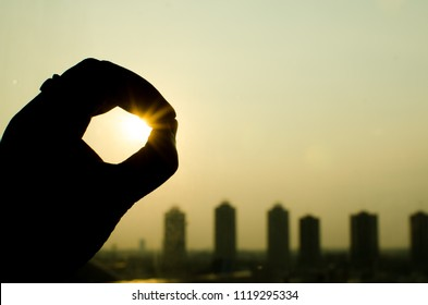 hand in silhouette concept touch the sun