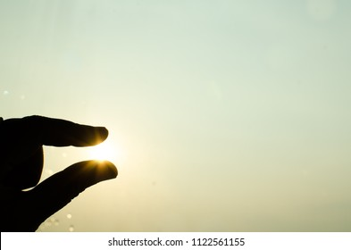 hand silhouette touch the sun