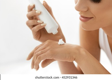 Hand Skin Care. Closeup Of Beautiful Smiling Young Woman With Nude Makeup Holding Cream Tube Applying Cosmetic Hand Cream On Her Soft Skin. Happy Healthy Female Taking Care Of Her Body. Beauty Concept