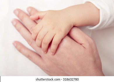Hand the sleeping baby in the hand of mother close up on the bed, New family and baby protection concept