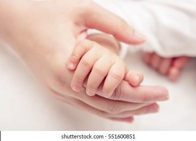 Hand the sleeping baby in the hand of mother close up (Soft focus and blurry)