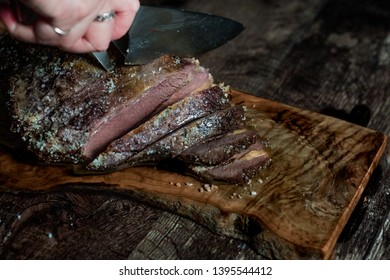 Hand slicing juicy grilled steak on a platter