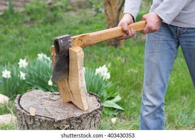 Hand slicing wood by axe