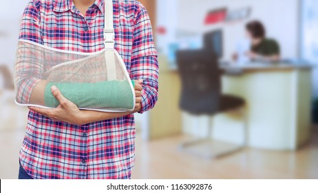 hand in a sling with broken arm in green cast isolated on blurred background working woman with office desk workplace in office.