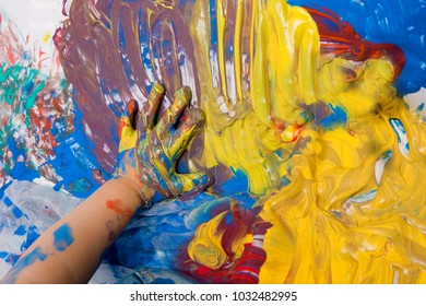 hand of a small child smearing colorful finger paint