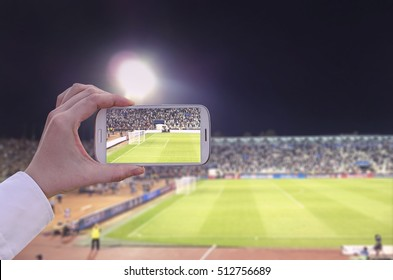 Hand with smart phone in a stadium taking pictures of a sport event