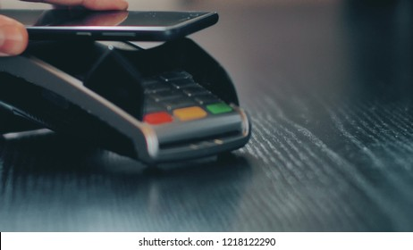 Hand with a smart phone using the POS terminal for payment by NFC technology