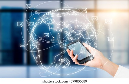 Hand with smartphone, globe with envelopes flying around over it. Window at background. Concept of communication.