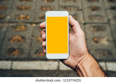 Hand with smartphone mock up copy space, man using modern contemporary mobile phone on the street in urban environment