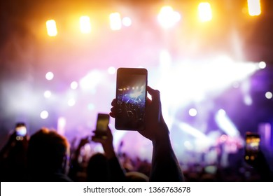 Hand with a smartphone records live music festival, live concert, live concert.