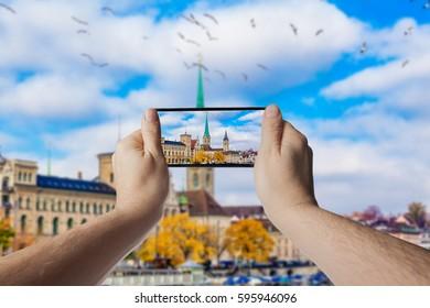 Hand with smartphone taken pictures of Zurich, Switzerland