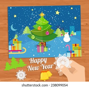 Hand with snowflake and New Year greeting card with decorated christmas tree, snowmans and gifts against the background of glowing windows of a night city. Raster version