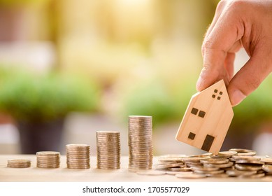 hand of someone put wooden house model on coins, money saving or investing for home lone or real estate concept