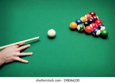 A hand of someone who is playing pool.