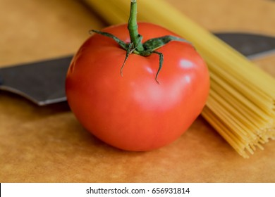 A hand of spaghetti and a knife of the background of a tomato